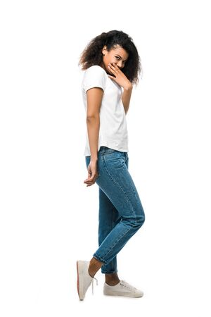african american girl covering face with hand and standing in blue jeans isolated on white