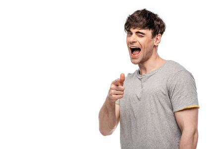 cheerful young man pointing with finger and winking at camera isolated on white