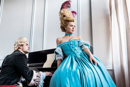 attractive victorian woman in blue dress standing near man in wig playing piano
