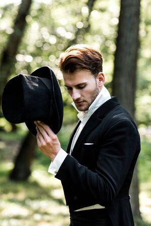 bell'uomo aristocratico che tiene il cappello mentre si trova in tuta