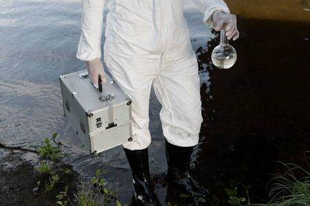 partial view of water inspector in protective costume holding inspection kit and flask at river Foto de archivo - 127995007