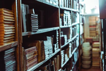 selective focus of retro books on wooden shelves in library Imagens