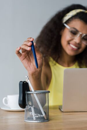 selective focus of pen holder and happy african american woman taking pen while using laptop