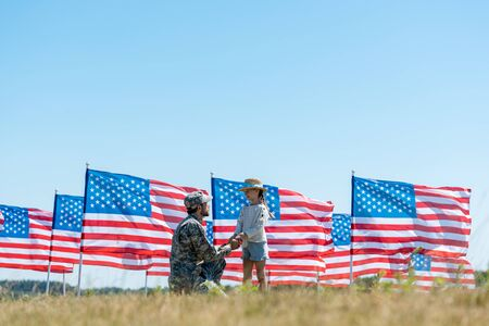 selective focus of military father holding hands with cute kid near american flags Imagens