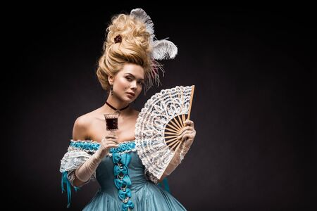 attractive victorian woman holding fan and wine glass on black