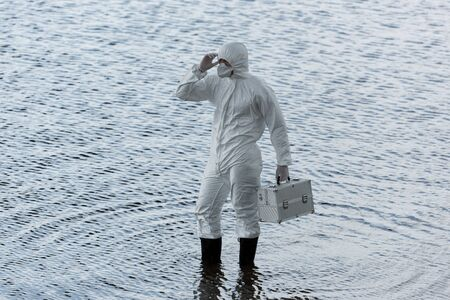 water inspector in protective costume holding inspection kit in river Foto de archivo - 127994823