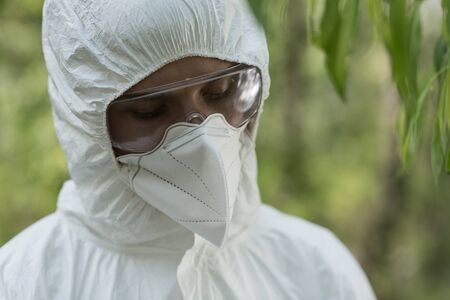 ecologist in protective costume, goggles and respirator looking down Stock Photo