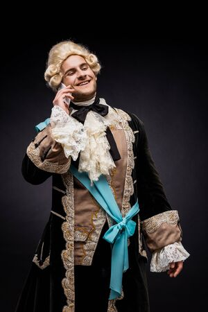 cheerful victorian man in wig smiling while talking on smartphone on black Reklamní fotografie