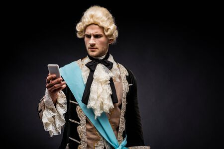 handsome victorian man in wig looking at smartphone on black 스톡 콘텐츠