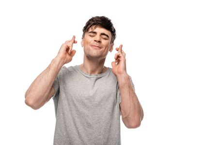 positive young man holding crossed fingers with closed eyes isolated on white Banque d'images - 127994685