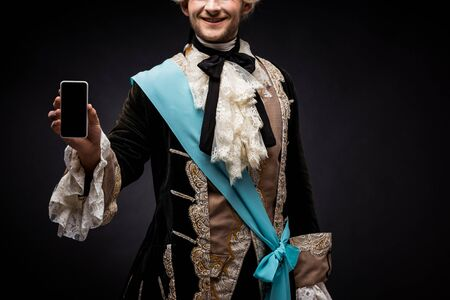 cropped view of happy victorian man holding smartphone with blank screen on black