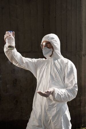 ecologist in protective costume and respirator holding bottle with soil sample Stock Photo