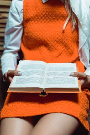 cropped view of woman in orange dress holding book in library Stock Photo