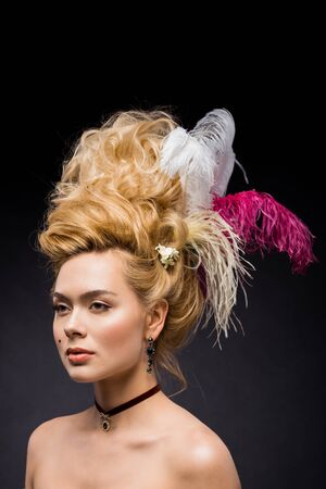 elegant and attractive woman with feathers in wig on black