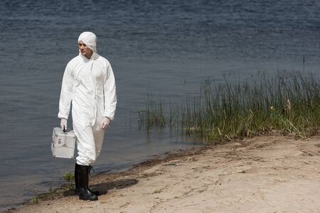 full length view of water inspector in protective suit holding inspection kit and standing on river coast 写真素材
