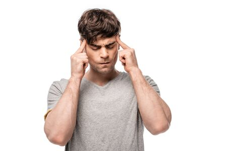 tired young man touching head with fingers while standing with closed eyes isolated on white