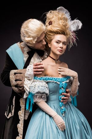 handsome victorian man looking at young beautiful woman in wig on black Фото со стока