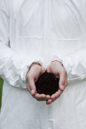 partial view of ecologist in protective costume holding handful of soil Stock Photo