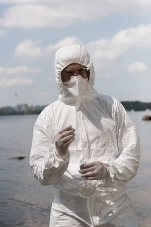 front view of water inspector in protective costume, latex gloves and respirator holding flask with water sample at river