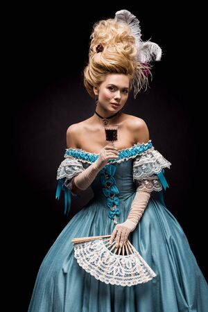 young victorian woman holding wine glass and fan on black