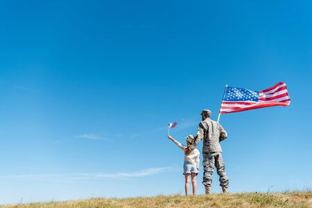 back view of child in straw hat and military father holding american flags while standing on grass