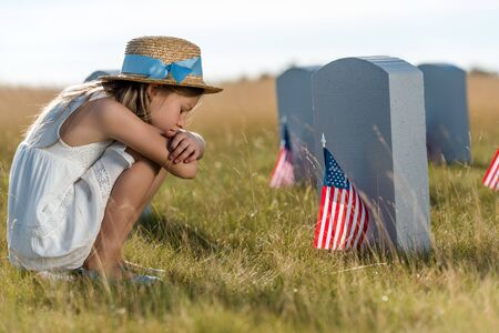 sad kid in straw hat sitting near headstones with american flags 스톡 콘텐츠