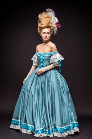 beautiful victorian woman in wig standing in blue dress on black