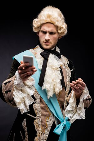 handsome victorian man holding smartphone on black