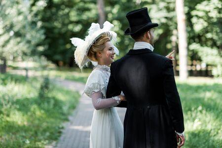 Feliz joven mujer victoriana de pie con el hombre con sombrero fuera Foto de archivo