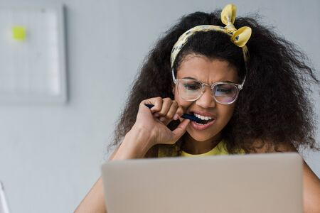 selective focus of emotional african american girl biting pen while looking at laptop