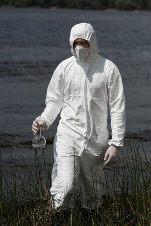 water inspector in protective costume, respirator and goggles holding flask with water sample Stock Photo