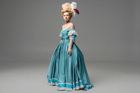 attractive victorian woman in wig and blue dress on grey