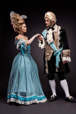 handsome victorian man and woman in wigs standing and holding hands on black