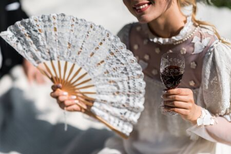 cropped view of happy young victorian woman holding fan and wine glass