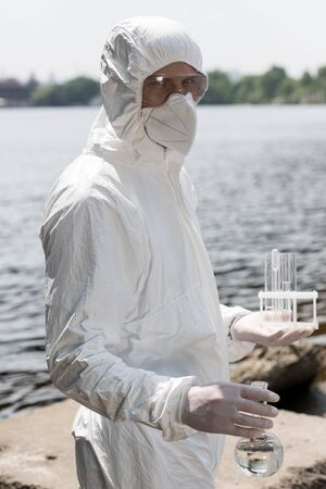 water inspector in protective costume, latex gloves and respirator holding flask and test tubes with water samples at river Stock Photo