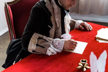 cropped view of victorian man holding feather and writing letter Фото со стока