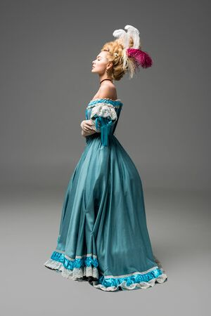 side view of pompous victorian woman in wig standing in blue dress on grey
