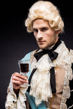 pompous victorian man in wig holding wine glass on black