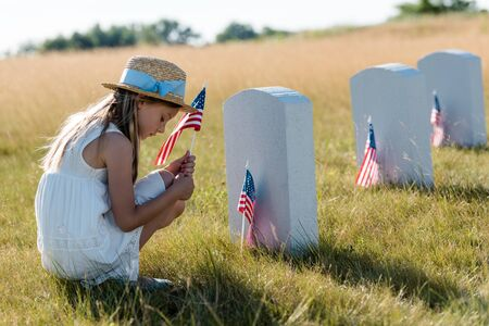 sad kid in straw hat sitting near headstones and holding american flag 스톡 콘텐츠