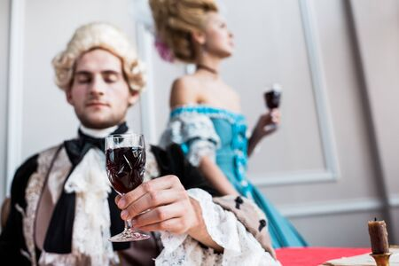 selective focus of victorian man in wig holding glass wine near pompous woman