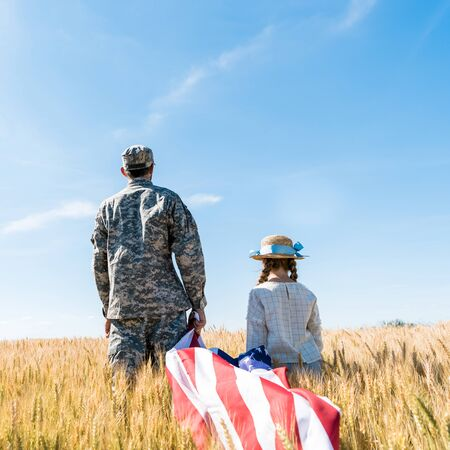 back view of soldier and kid standing in field and holding american flag