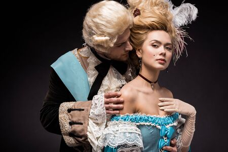 handsome victorian man looking at young woman in wig on black