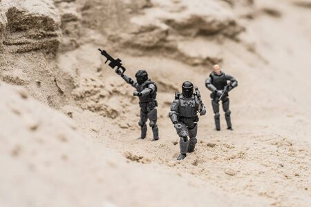 selective focus of plastic toy soldiers on sand dune with guns