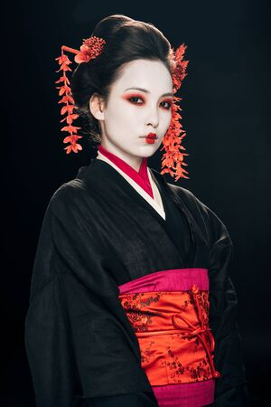 geisha in black and red kimono and flowers in hair isolated on black Stok Fotoğraf - 128057914