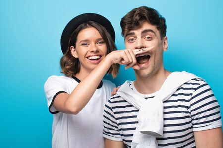 cheerful girl holding finger with drawn mustache near face of young man on blue background