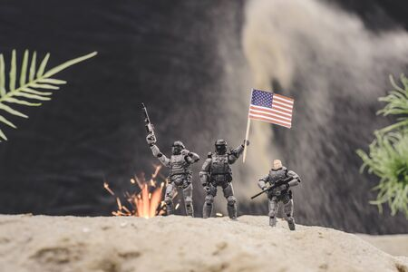 selective focus of toy soldiers with guns and american flag standing near explosion on sand dune