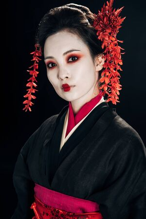 beautiful geisha in black and red kimono and flowers in hair looking at camera isolated on black 版權商用圖片