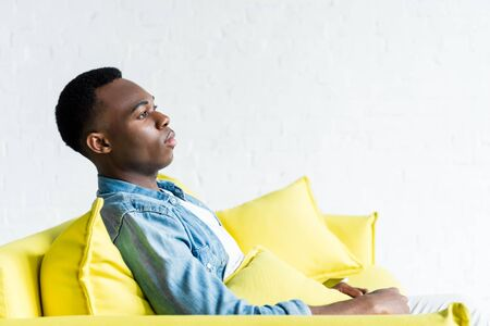 side view of calm african american man sitting on couch at home