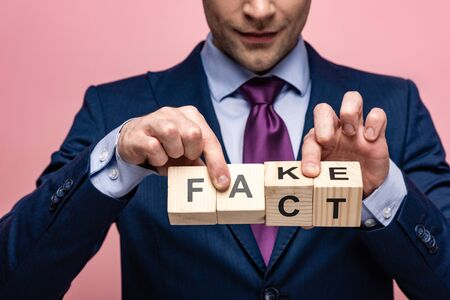 cropped view of businessman showing wooden cubes with fake fact lettering isolated on pink Stock Photo