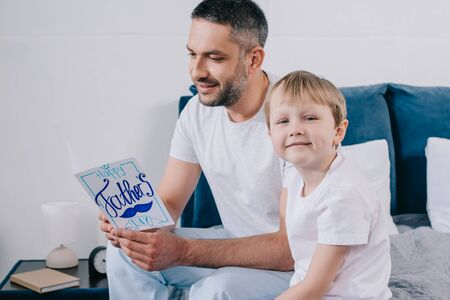 cheerful father holding fathers day greeting card while sitting near smiling son